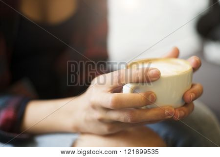 Girls hands holding a freshly brewed cup of coffee