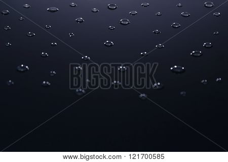The isolated water droplets on a dark background.
