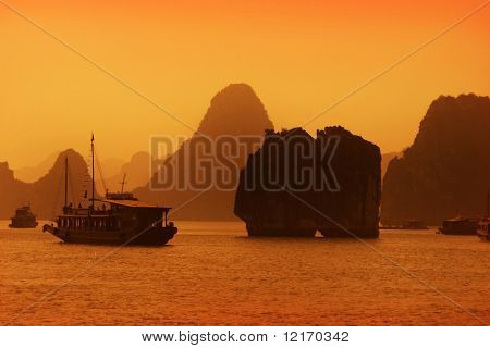 Limestone outcrops in Ha Long Bay and tourist boat at sunset