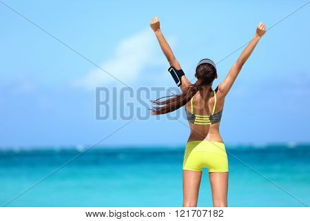 Strong fitness athlete arms up in success on summer beach after cardio training workout. Female runner woman running winning reaching goal achievement during strength training showing power.
