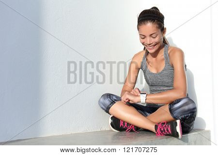 Fitness girl using activity tracker smartwatch as heart rate monitor for workout or tracking her weight loss improvement. Woman runner living a healthy life. Wearable tech.