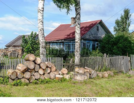 Old Rural House With Pile Of Big Wooden Chocks In Front