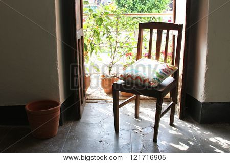 Chair In Front Of Open Balcony Door With Flowers