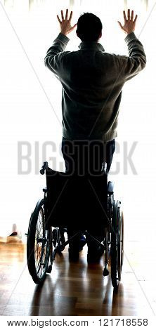 Young Man Standing With The Wheelchair By The Window