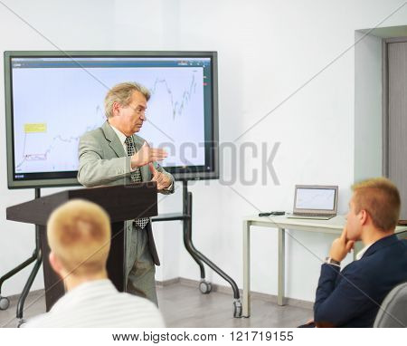Businessman Giving A Presentation On Flipchart. Teamwork Concept