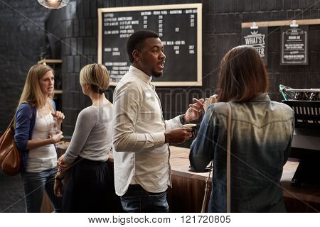 Good-looking African man talking with a female friend at the modern counter of a trendy coffee shop, while waiting for their order to be made, with two women chatting in the background