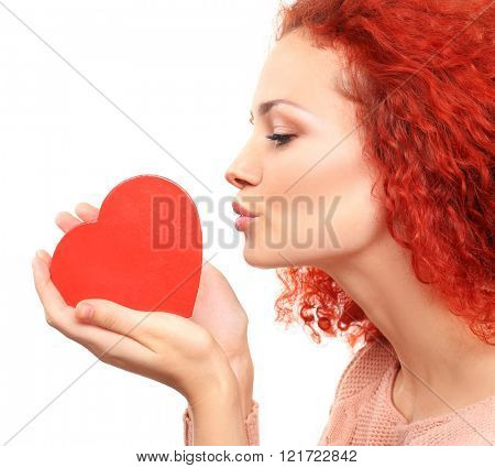 Red-haired young woman holding and kissing heart, isolated on white