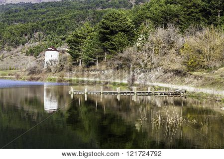 Stone wind mill and wooden pier reflection on Cubuk lake near Goynuk, Bolu