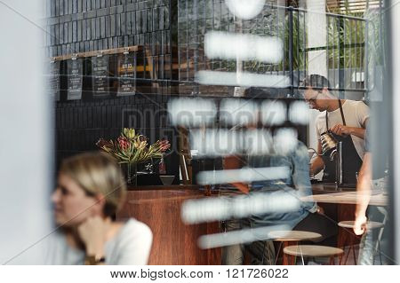 Shot of the front window of a coffee shop through which you can see the barista working behind the counter, customers at the counter and at tables, the writing on the pane of glass, and reflections