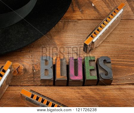 blues harps in wood background and word blues in letterpress type