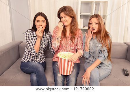 Three afraid girls wathing movie and eating popcorn poster