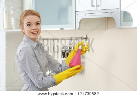 Young woman using spray cleanser to clean a kitchen cupboard
