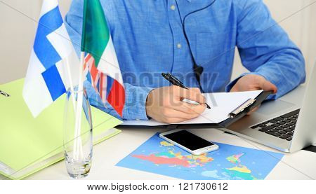 Young man talking on headset and making notes in the office of travel company