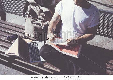 Closeup photo man wearing white tshirt sitting city park and writing notebook. Studying at the Unive