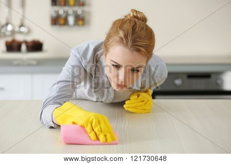 Young woman scrubbing the bar in kitchen