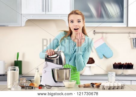 Young woman using a food processor to make a dough