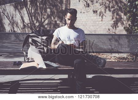 Photo man wearing white tshirt sitting city park bench and writing textbook. Studying at the Univers
