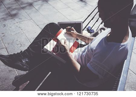 Photo man sitting city park and texting message notepad. Studying at the University, working project