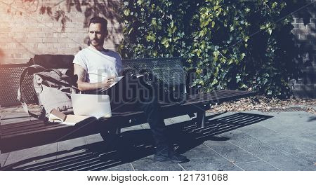 Bearded man wearing white tshirt sitting city park bench and reading book. Studying at the Universit