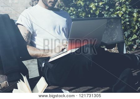 Photo student sitting city park bench and texting message notebook. Using wireless internet.Studying