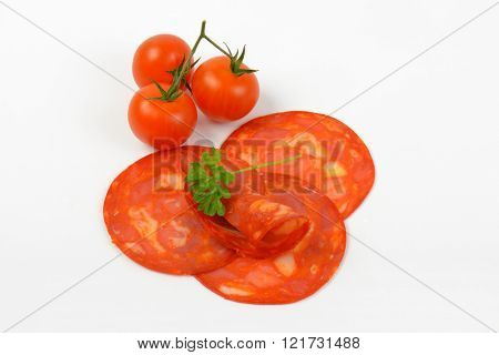 slices of chorizo salami and cherry tomatoes on white background - close up