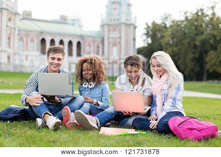 Young student with laptop outdoors