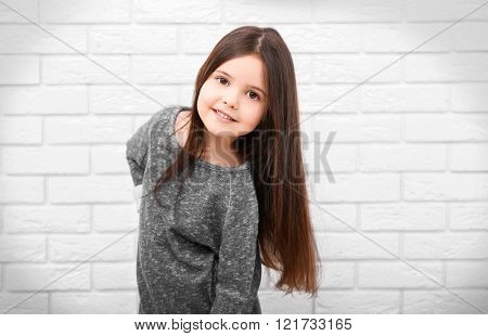 Little girl on a white brick wall background