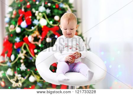 Funny baby girl sitting in armchair On Christmas tree background