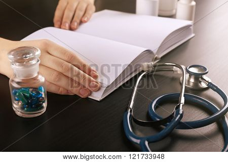 Human's hands on medical book with pills and blue stethoscope, closeup