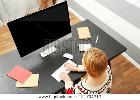 Back view of blond girl using modern computer in office