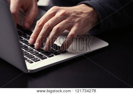 Male hands typing on laptop keyboard at table closeup