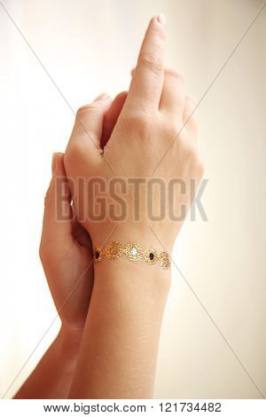 Golden flash tattoo on female wrist over white background