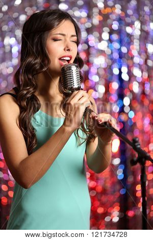 Young cute woman singing against bright glitter background
