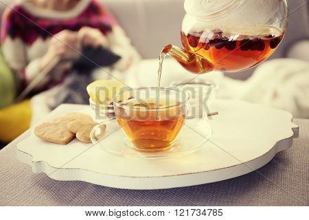 Pouring tea into cup, home atmosphere