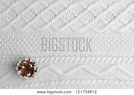 Beautiful simple winter background with pine cone on knitted texture