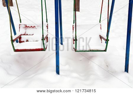 Empty swing covered with snow