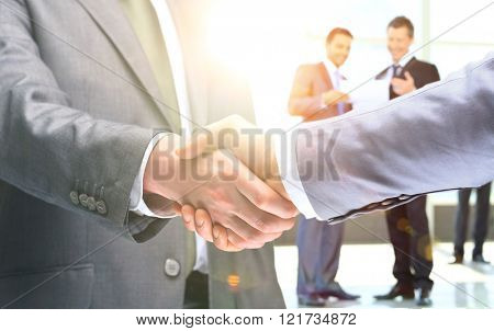 Close-up of business people shaking hands to confirm their partnership