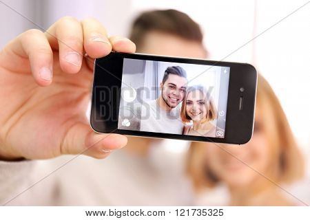 Young couple in love taking photo of their self with mobile phone, close up