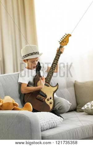 Little boy playing guitar on a sofa at home