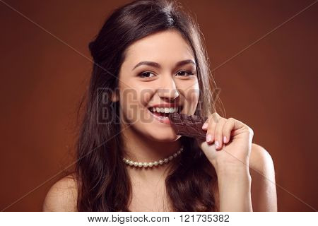 Portrait of attractive young woman with chocolate on brown background, close up