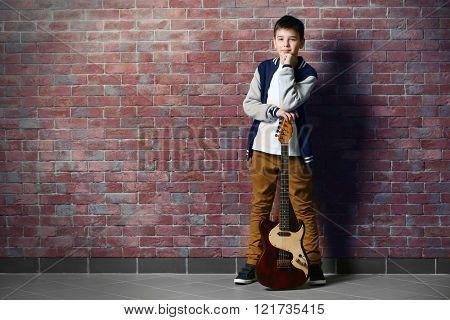 Cute little boy with guitar standing near brick wall