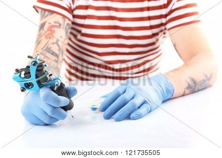 Tattoo master working in blue medical gloves with tattoo machine, close up