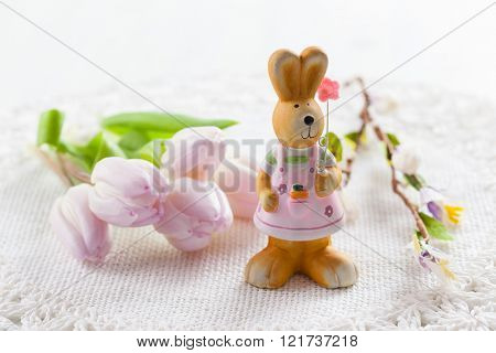 Easter bunny with painted eggs with fresh tulips