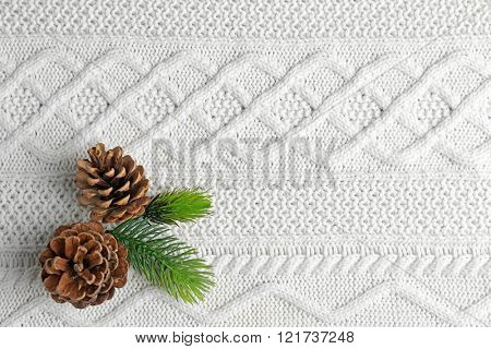 Beautiful simple winter background with pine cones on knitted texture