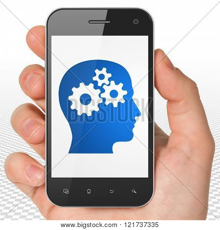 Education concept: Hand Holding Smartphone with Head With Gears on display