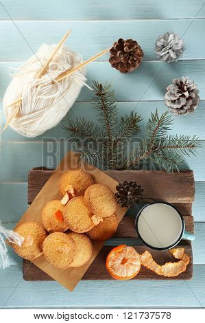 Christmas composition with a scarf, cookies and decorations on a blue table