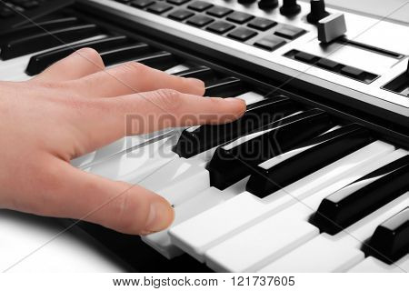 Male hand playing of synthesizer closeup
