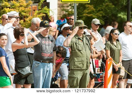 ALPHARETTA, GA - AUGUST 2015:  Combat veterans attending the annual Old Soldiers Day parade salute the American flag as it passes by, on August 1, 2015 in Alpharetta, GA.