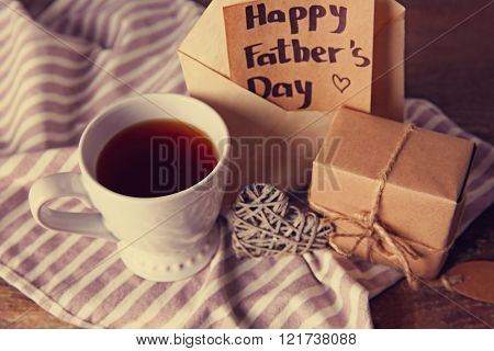 Greeting card for Happy Father's Day with tea cup and gift box on wooden background