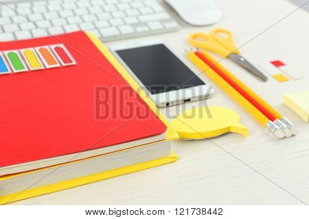 Workplace with mobile phone, keyboard and stationery on light table